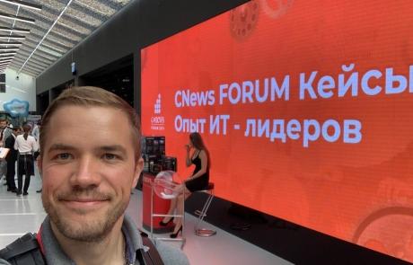 Селфи Фёдора Жернового на фоне красного экрана с надписью Cnews FORUM Кейсы Опыт ИТ - лидеров